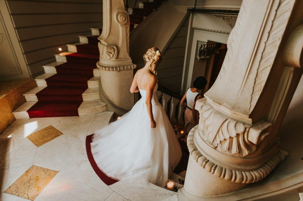 Braut geht die Treppen auf Schloss albrechtsberg zum Gartensaal zum Trausaal. Schloss Albrechtsberg als Barockes Gebäude mitten in der Dresdner Innenstadt als einer der drei Elbschlösser.